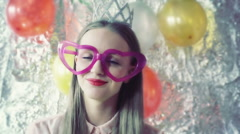 Pretty wearing heart glasses and crown and smiling to the camera Stock Footage