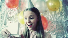 Happy girl wearing birthday cup and looking on her gift, steadycam shot Stock Footage