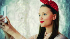 Pretty girl wearing red bow and doing selfies on smartphone Stock Footage