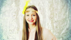 Pretty girl wearing golden band with feathers and smiling to the camera Stock Footage