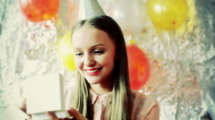 Pretty girl wearing cup and looking on her birthday present, steadycam shot Stock Footage