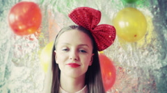 Pretty birthday girl wearing red bow and smiling to the camera, steadycam shot Stock Footage
