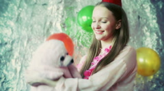 Birthday girl cuddling toy and smiling to the camera, steadycam shot Stock Footage