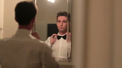 Handsome groom adjusts his bowtie. Reflection in the mirror Stock Footage