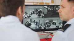 4K Security workers in system control room looking at CCTV on computer screens.  - stock footage