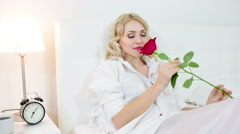 Sexy lady on the white bed with red roses Stock Footage
