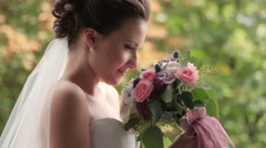 Brunette bride with wedding bouquet on green background - stock footage