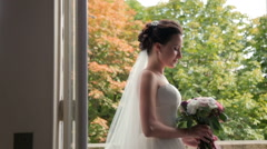 Beautiful brunette bride with wedding bouquet standing near the window - stock footage