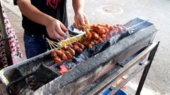 Vendor preparing delicious barbecue chicken and beef satay on charcoal grille Stock Footage