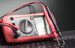 Multimeter and laptop - stock photo