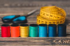Sewing background with color threads, meter and scissors - stock photo