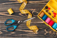 Stock Photo of Sewing background with color threads, meter and scissors