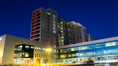 Stock Video Footage of Generic Health Care Modern Hospital Exterior Building at night. Time Lapse