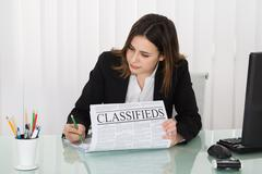 Young Businesswoman Highlighting Advertisement On Newspaper In Office Stock Photos