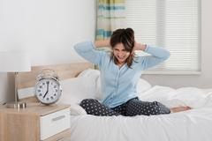 Exhausted Young Woman Awakened By An Alarm Clock In Her Bedroom Stock Photos