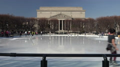 Ice skating on Mall in Washington, DC.  National Archives in background, Stock Footage