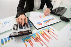 Young Businesswoman Analyzing Report On Chart With Calculator Stock Photos