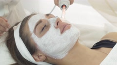 Close up darsonvalization girl face with clay mask in saloon. Cosmetic procedure Stock Footage