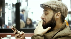 Man relaxing in cafe smoking playing with cellphone Stock Footage