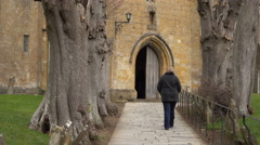 Woman walking to ancient St James Church Chipping Campden 4K Stock Footage