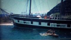1963: Dog riding canoe boy feeds dolphin pirate ship. Stock Footage