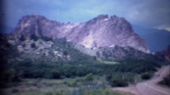 Stock Video Footage of 1963: Cars driving past scenic mountain rock formation gap.