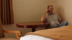 An interior shot of a man on phone in hotel room Stock Footage