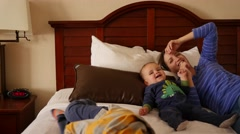 Interior dolly shot of a family on hotel room bed Stock Footage