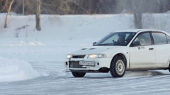 SLOW: A white sport car turns on a winter ice road Stock Footage