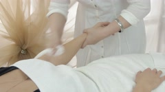 Stock Video Footage of Professional cosmetologist wipe left girl hand in beauty saloon. Medium shot