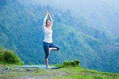 Woman in yoga asana Vrikshasana tree pose outdoors Stock Photos