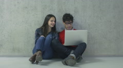Male and female students are sitting in a college hallway and working on laptop Stock Footage