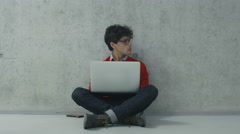 Hispanic male student is sitting in a college hallway and working on a laptop Stock Footage