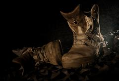 Military boots on camouflage net and black backround Stock Photos