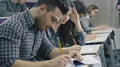 Footage of hispanic student writing with pen on paper in a collage classroom - stock footage