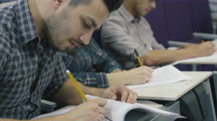 Footage of students with pens and papers in a collage classroom during lecture Stock Footage