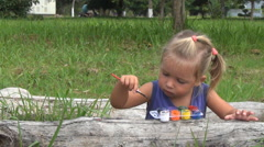 Girl draws picture with paints on the wood Stock Footage
