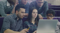 Group of students are sitting in a college classroom and looking at a laptop pc - stock footage