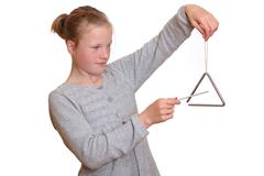 A young girl plays with a triangle Kuvituskuvat