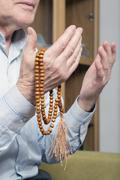 Praying hands of an old man with rosary beads - stock photo
