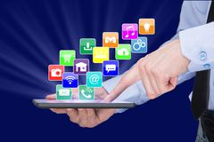 Businessman holding a tablet pc with mobile applications icons on virtual screen Stock Photos