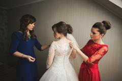 Happy buddies helps bride getting ready for her wedding day in the morning - stock photo