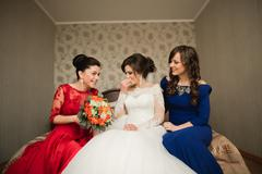 Happy buddies helps bride getting ready for her wedding day in the morning Stock Photos