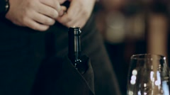 Bearded sommelier opens the bottle of wine for visitors Stock Footage