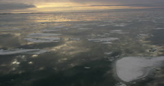 Reflection of sky between passing chunks of sea ice in the arctic evening Stock Footage