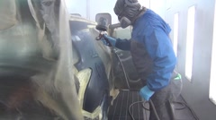 Car painter is painting the body work of a car in a paint box Stock Footage