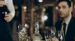 Sommelier pouring red wine into glass of restaurant guests Stock Footage