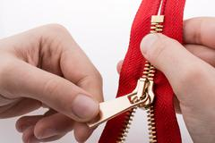 Hand holding zipper - stock photo