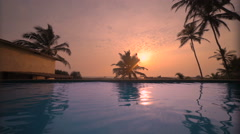 Sea beach resort swimming pool with sunset reflection Stock Footage