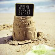Signboard with the text spring break on a sandcastle Stock Photos